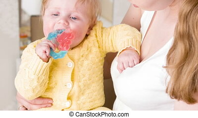 Happy rattle in baby hands - Cheerful little guy is playing...