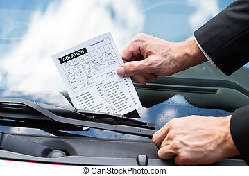 Parking Ticket On Cars Windshield - Close-up Of A Man Taking...