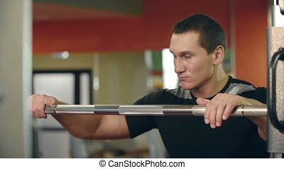 Body Workout - Close up of a man taking the barbell from the...