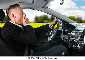Businessman Yawning While Driving Car - Portrait Of A Young...