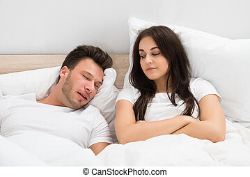 Woman Looking At Man Snoring In Bed At Home - Angry Young...