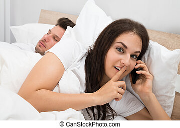 Woman Talking Privately On Cellphone While Her Husband...