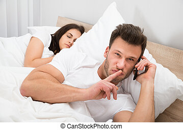 Man Talking Privately On Cellphone While His Wife Sleeping...