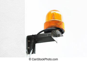 Revolving amber light beacon or siren at corner of building