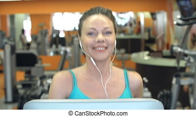 Cardio in a Gym - Front view of fit lady cardio training and...