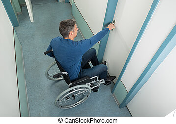 Man Sitting On Wheelchair Opening Door - High Angle View Of...