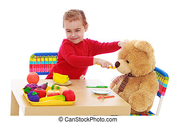 Little girl plays with a teddy bear