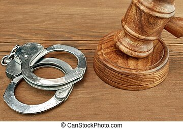 Judges Gavel And Handcuffs On Wood Rough Background -...