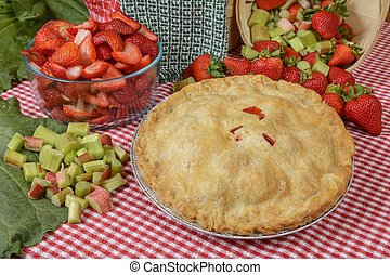 Strawberry-Rhubarb Pie on a country table with strawberries...