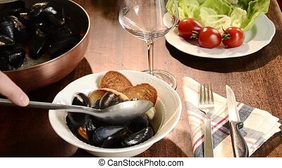 mussels marinara in copper pot with salad and toasts