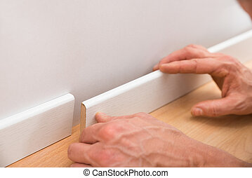 Person Applying Skirting On Wall - Close-up Of A Persons...