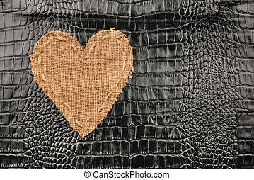 The symbolic heart from burlap lies on a crocodile leather,...