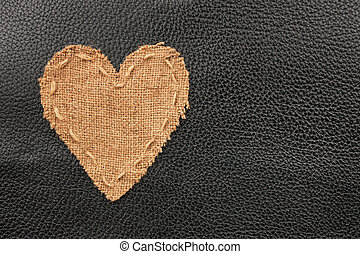 The symbolic heart from burlap lies on a natural leather, as...