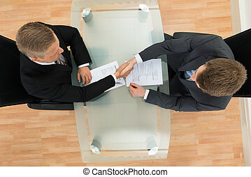Two Businessman Shaking Hands - Elevated View Of Two...