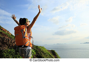 cheering woman backpacker on seaside mountain enjoy the view...
