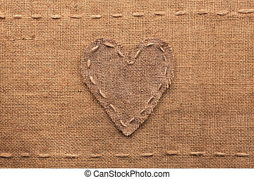 Heart made of burlap lies on a sacking background,can be...