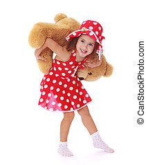 Smiling little girl playing with a Teddy bear