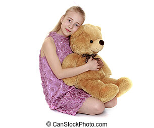 Blonde teen girl hugging a big Teddy bear- isolated on white...