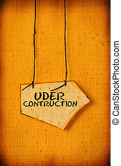 under contrction - Close up of handmade paper tag with UNDER...