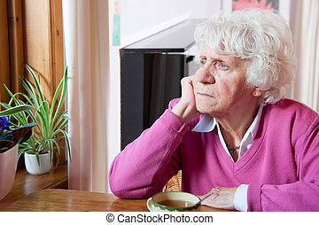 Depressed elderly woman sitting at the table - Elderly...