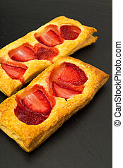 puff pastry slices with strawberry on black slate stone...