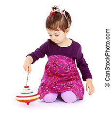Very little girl sitting on the floor and spinning the...