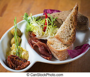 Antipasto. Dried tomatoes, olives, prosciutto and bread in a...