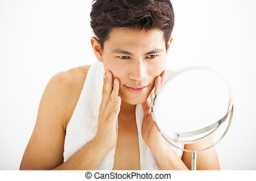 Young man touching his smooth face after shaving