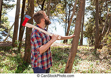 Portrait of an attractive young lumberjack who walks through...
