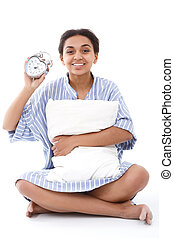 Smiling woman sitting with pillow and alarm clock - Time is...