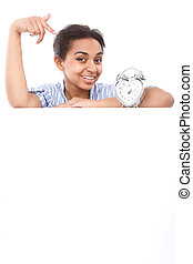 Smiling mulatto girl pointing on alarm clock - Glance here...