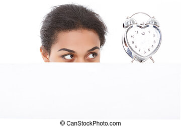 Pleasant woman fixedly looking at alarm clock - Looking...