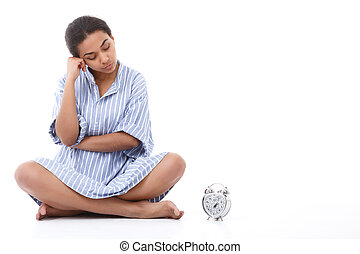 Attractive young woman sitting near alarm clock - Looking...