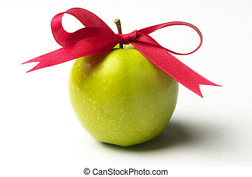 Green apple and red ribbon bow isolated over white...