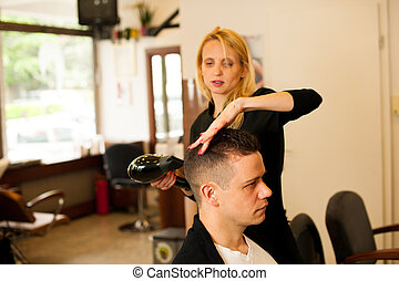 Female hairdresser cutting hair of smiling man client at...