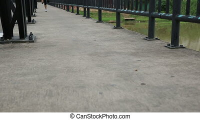 Runner athlete running on iron bridge. woman fitness jogging...
