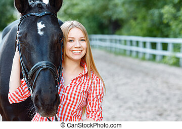 Smiling girl taking care of the horse - True friend...