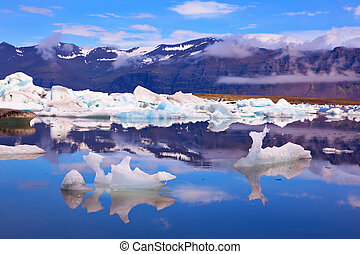 Icebergs and ice floes of freakish forms are reflected in...