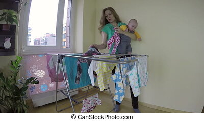 mother with baby laundry - Mother woman with newborn baby on...