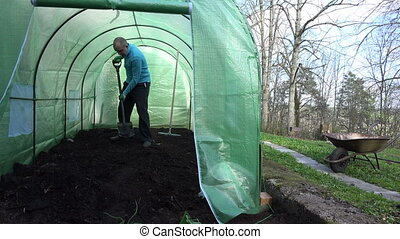 man compost greenhouse - young man gardener work hard with...