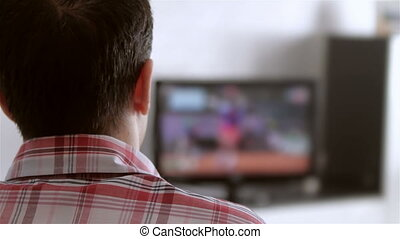 Man watching television in living room Shot from behind