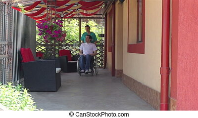 Nurse walking with male patient in a wheelchair