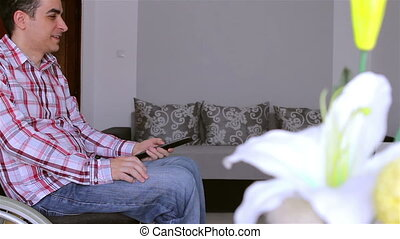 Man in wheelchair watching tv - Happy young disabled man...