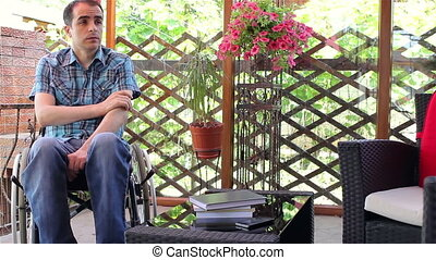 Young man in wheelchair feeling sad or worried outside.