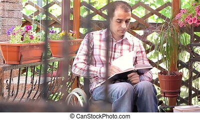 Young man in wheelchair reading - Young disabled in...