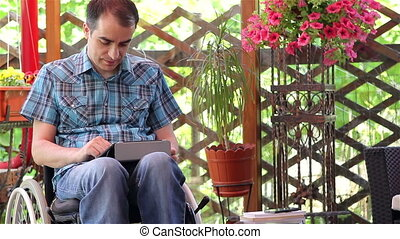 Man on wheelchair using tablet pc - Young man on wheelchair...