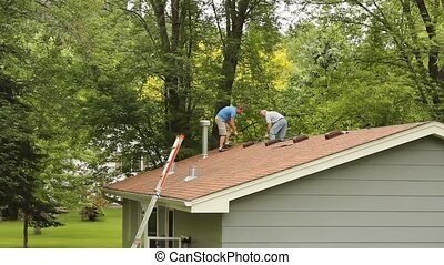 Roofing work - Two men are tearing off shingles from an old...