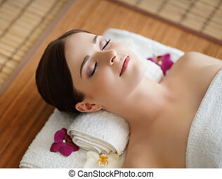 Young, beautiful and healthy woman in spa salon. Traditional...