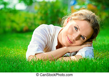 pacification - Beautiful smiling woman lying on a grass...