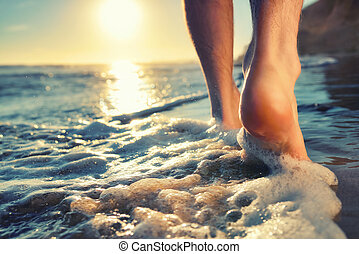 Enjoying a barefooted walk at the ocean - Closeup of a mans...